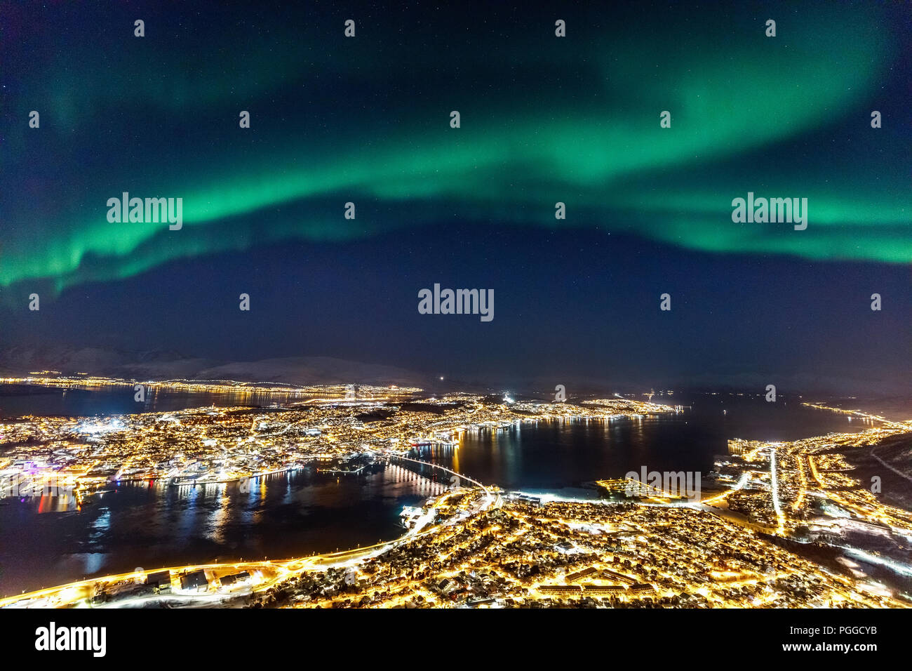 Incredible Northern lights Aurora Borealis activity above town of Tromso in Northern Norway - Stock Image