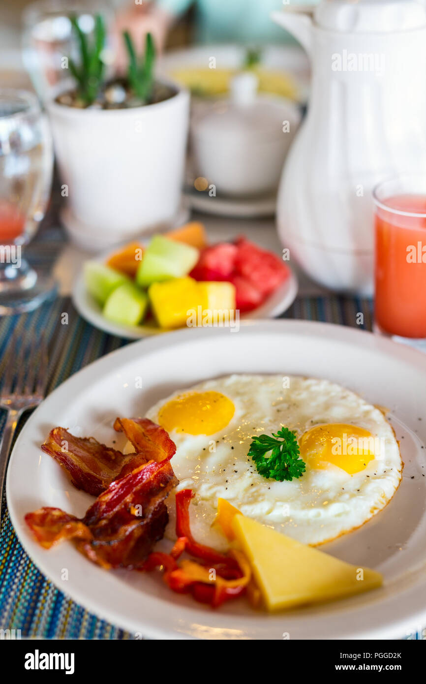 Delicious breakfast with fried eggs and bacon - Stock Image