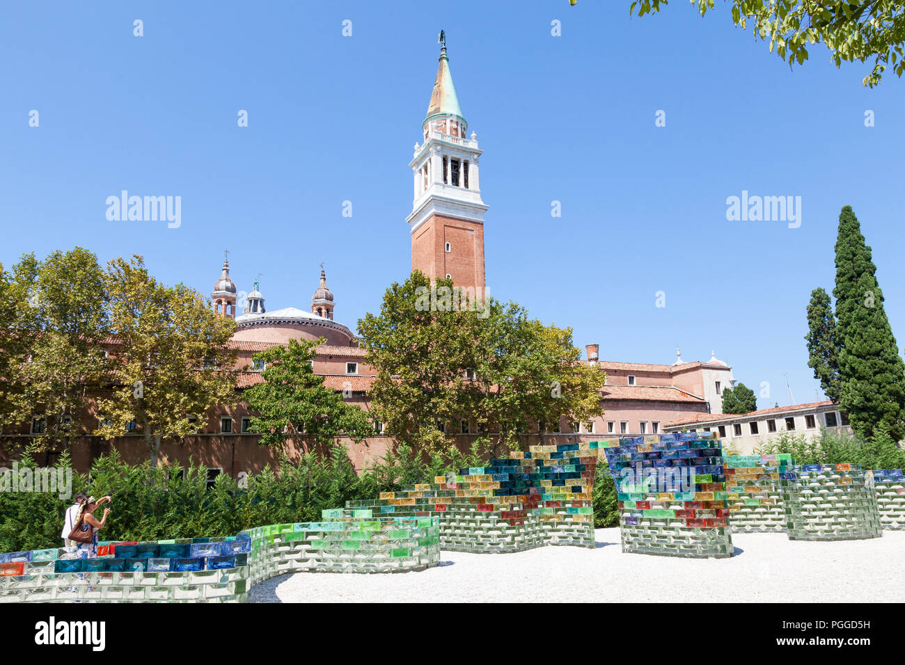 Qwalala glass wall by American artist Pae White for Biennale, Venice, Italy on San Giorgio Maggiore Island with the campanile of the church, tourists  - Stock Image