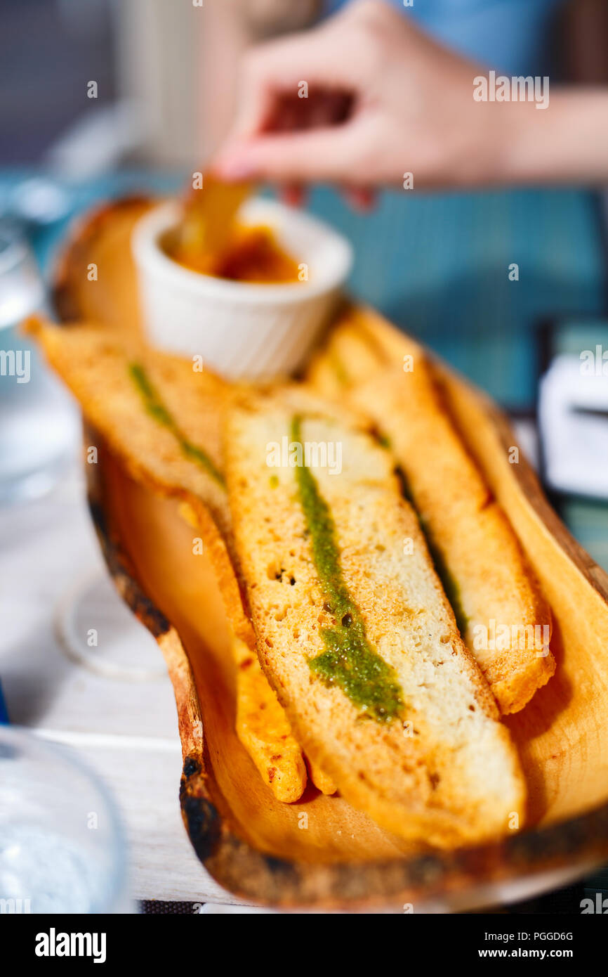 Crispy white bread baguette topped with pesto served for snack or appetizer at restaurant - Stock Image
