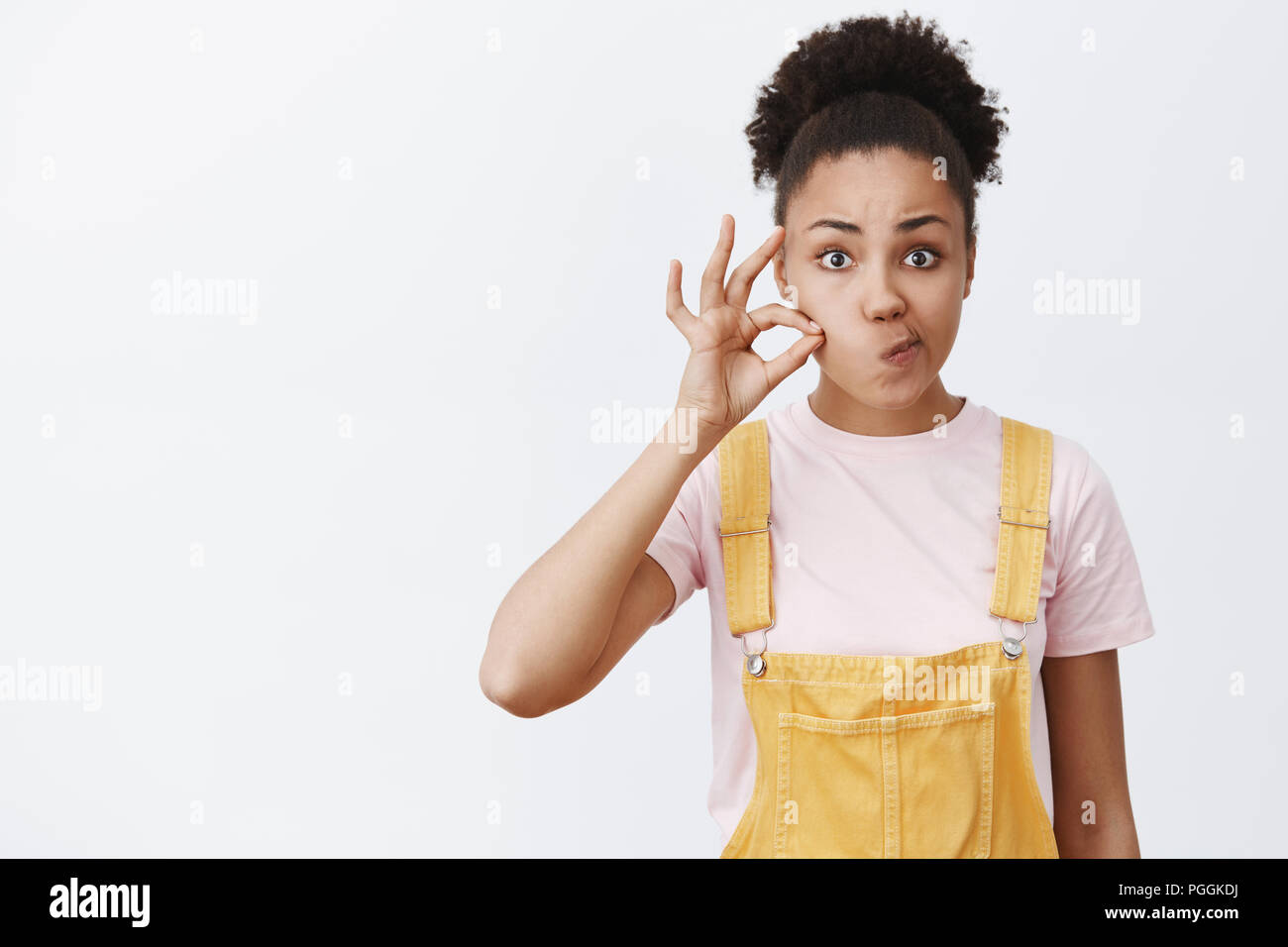 Zipping my mouth forever, secret safe. Portrait of charming serious African American woman making promise, shutting lips with invisible zip, pouting mouth right and holding finger near cheek - Stock Image