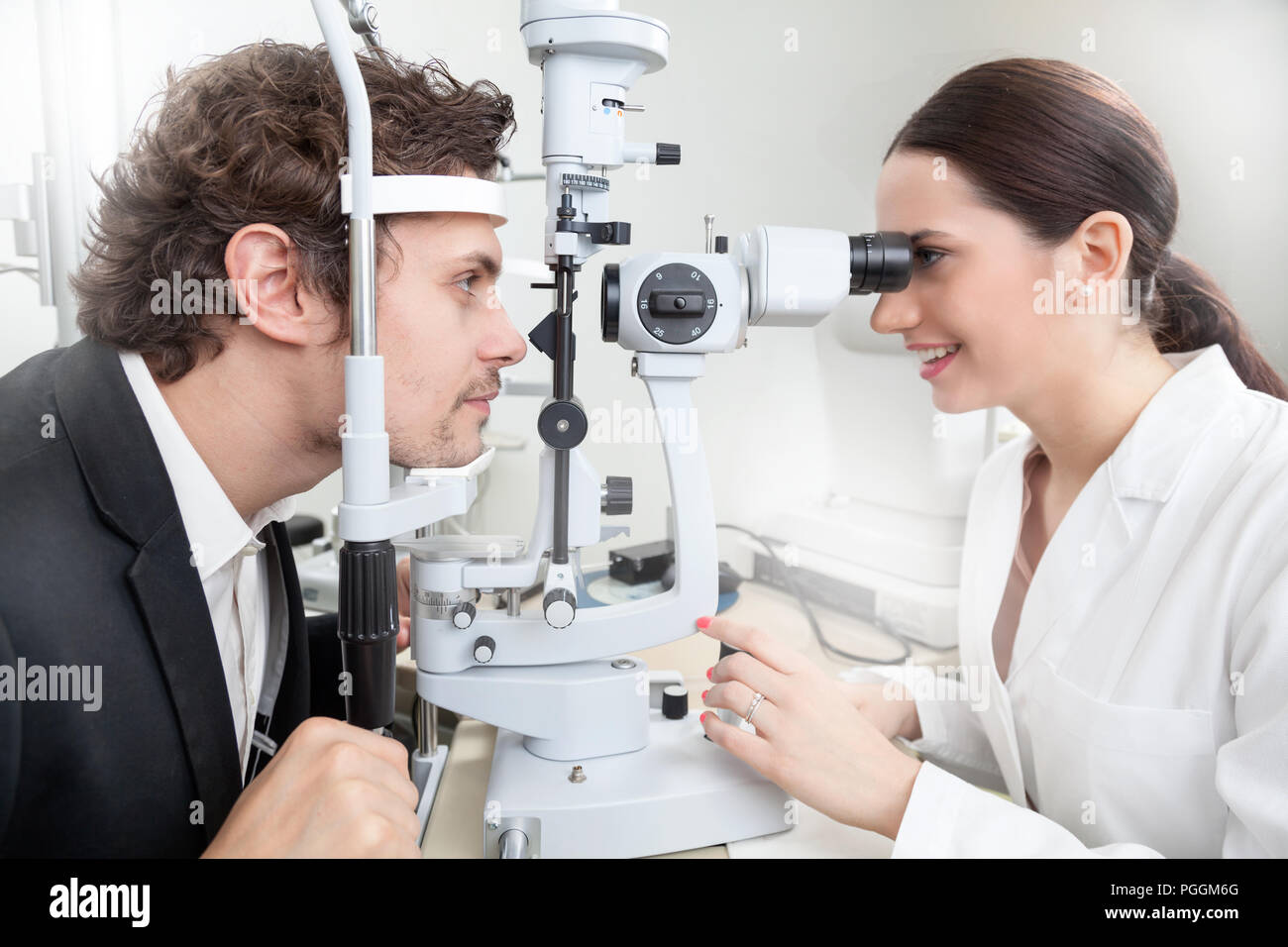 A man having an eye test with Slit Lamp / female doctor in ophthalmology clinic doing retina cornea exam diagnostic with vision of patient by modern c - Stock Image