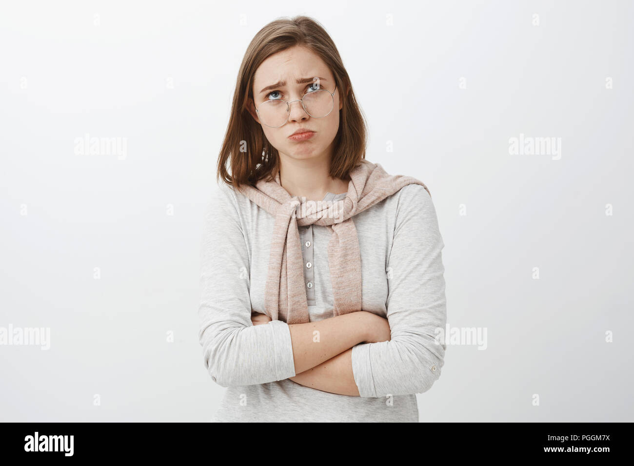 Sad gloomy offended silly girl in glasses and cute outfit folding lips, pouting frowning and looking up while complaining being offended whining over cruel and unfair life over gray background - Stock Image