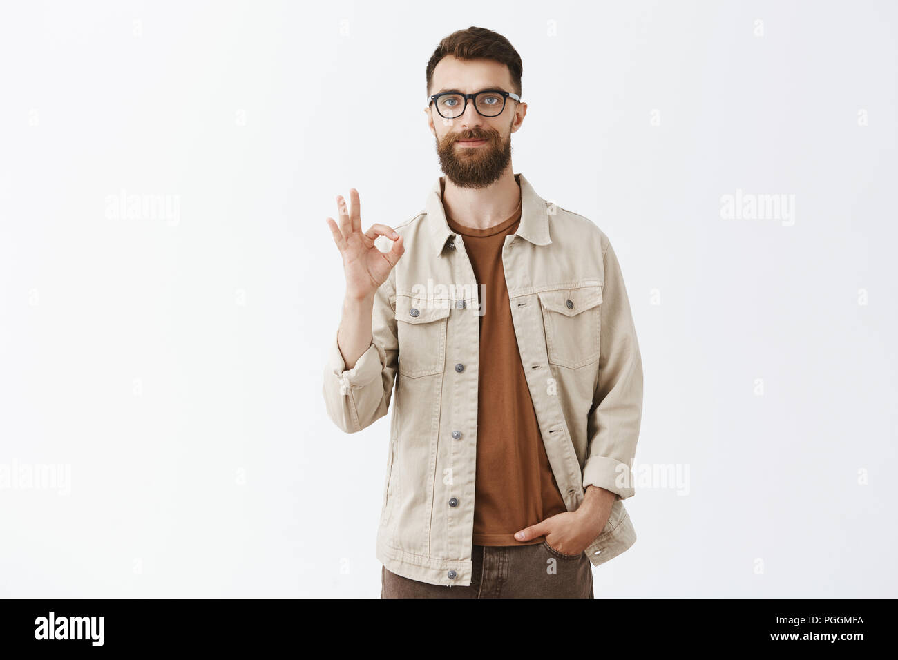 Calm friendly handsome caucasian guy with long beard and short hairstyle showing excellent or ok gesture with circled fingers smiling giving positive feedback or confirming plan fulfilled perfectly - Stock Image