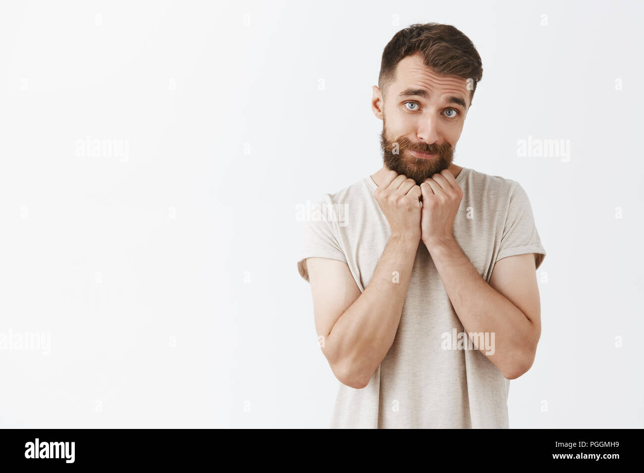 Studio shot of cute and tender masculine european guy with long beard and moustache leaning on palms looking silly and touched with girly smile standing charmed over gray background - Stock Image
