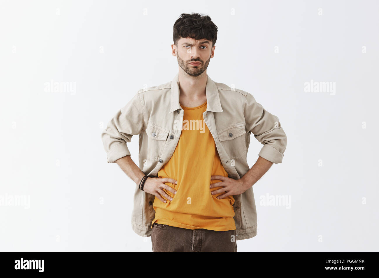 Portrait of intense doubtful and dissatisfied handsome caucasian bearded guy in trendy outfit holding hands on waist raising eyebrow in suspicious and disbelief pose over gray background - Stock Image