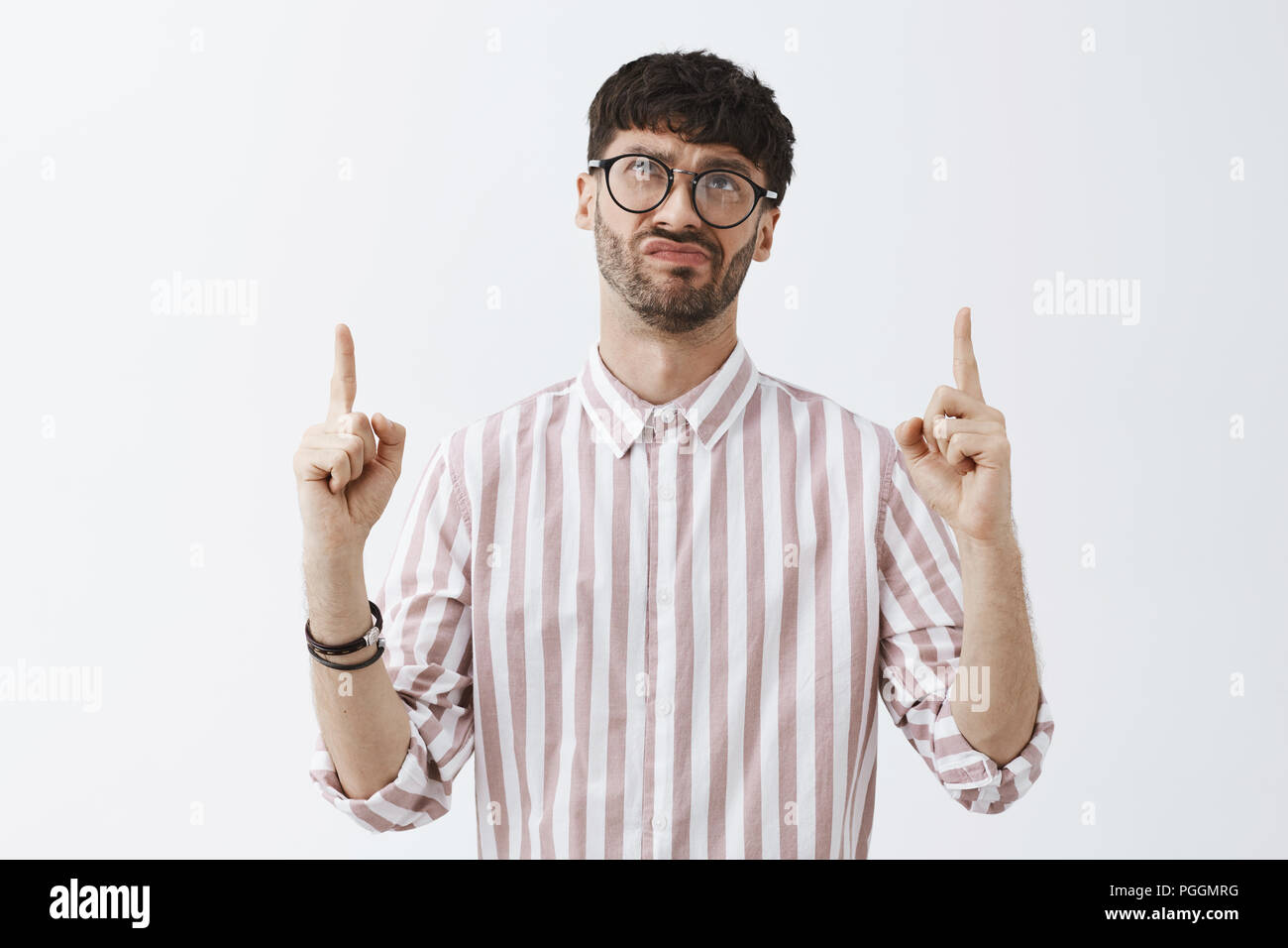 Waist-up shot of upset disappointed and snobbish good-looking guy in glasses and striped shirt pointing and looking up frowning and smirking from dislike being unimpressed and dissatisfied - Stock Image