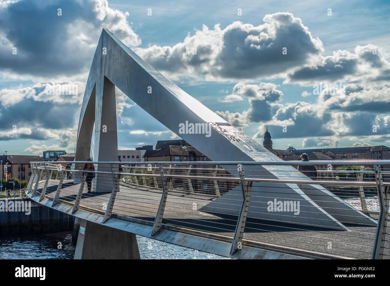 Pedestrians crossing the Tradeston bridge aka  Squiggly Bridge (2009) over the River Clyde in Glasgow city centre, Scotland. - Stock Image