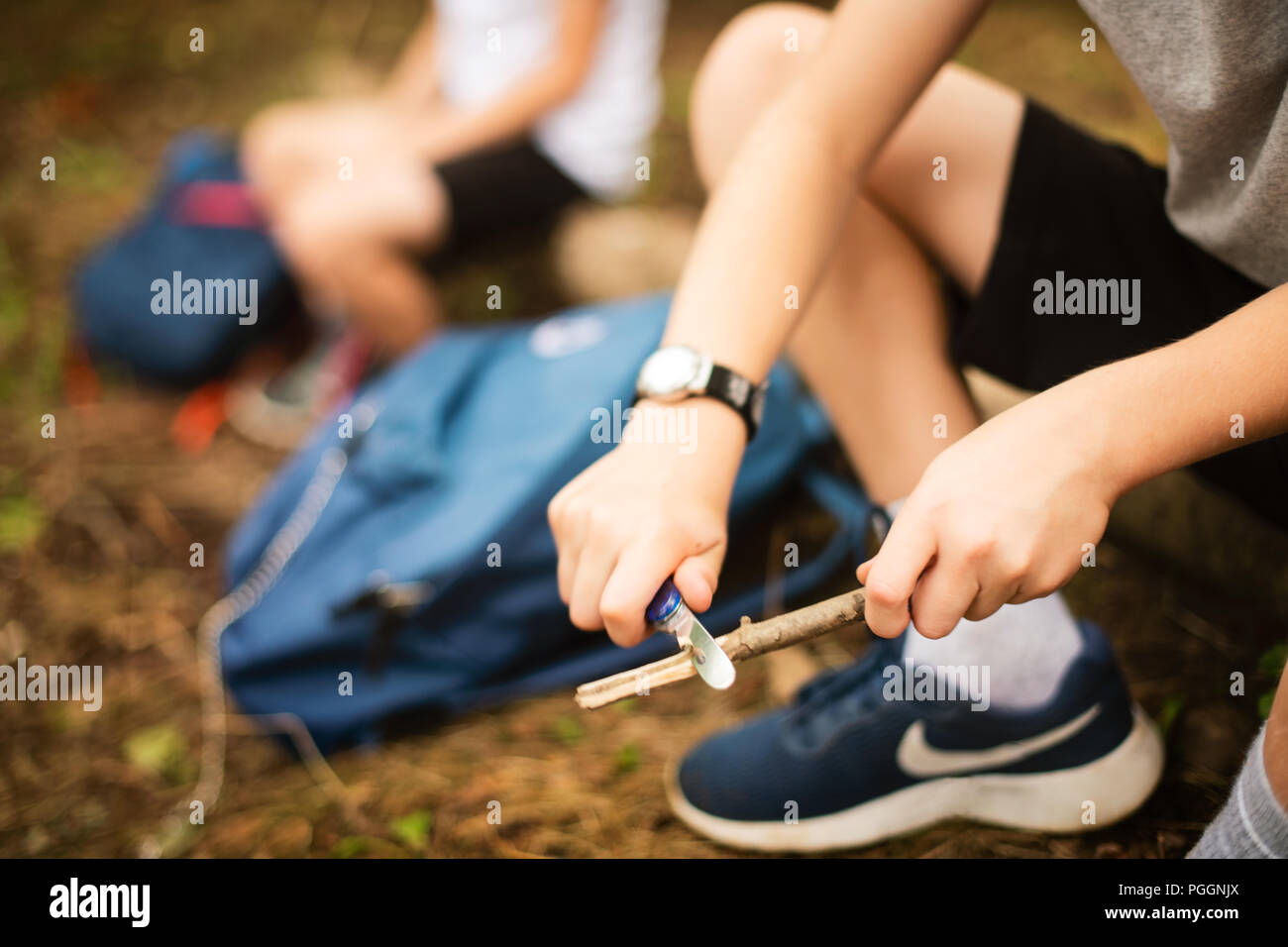 Boys whittling sticks to make pegs Stock Photo