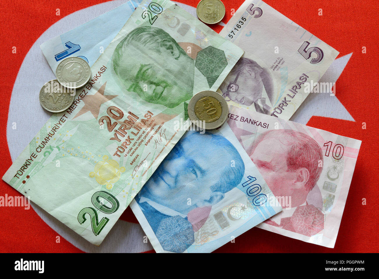 Turkish Lira bills and coins on turkish flag. The Turkish Lira is the national currency of Turkey. Stock Photo