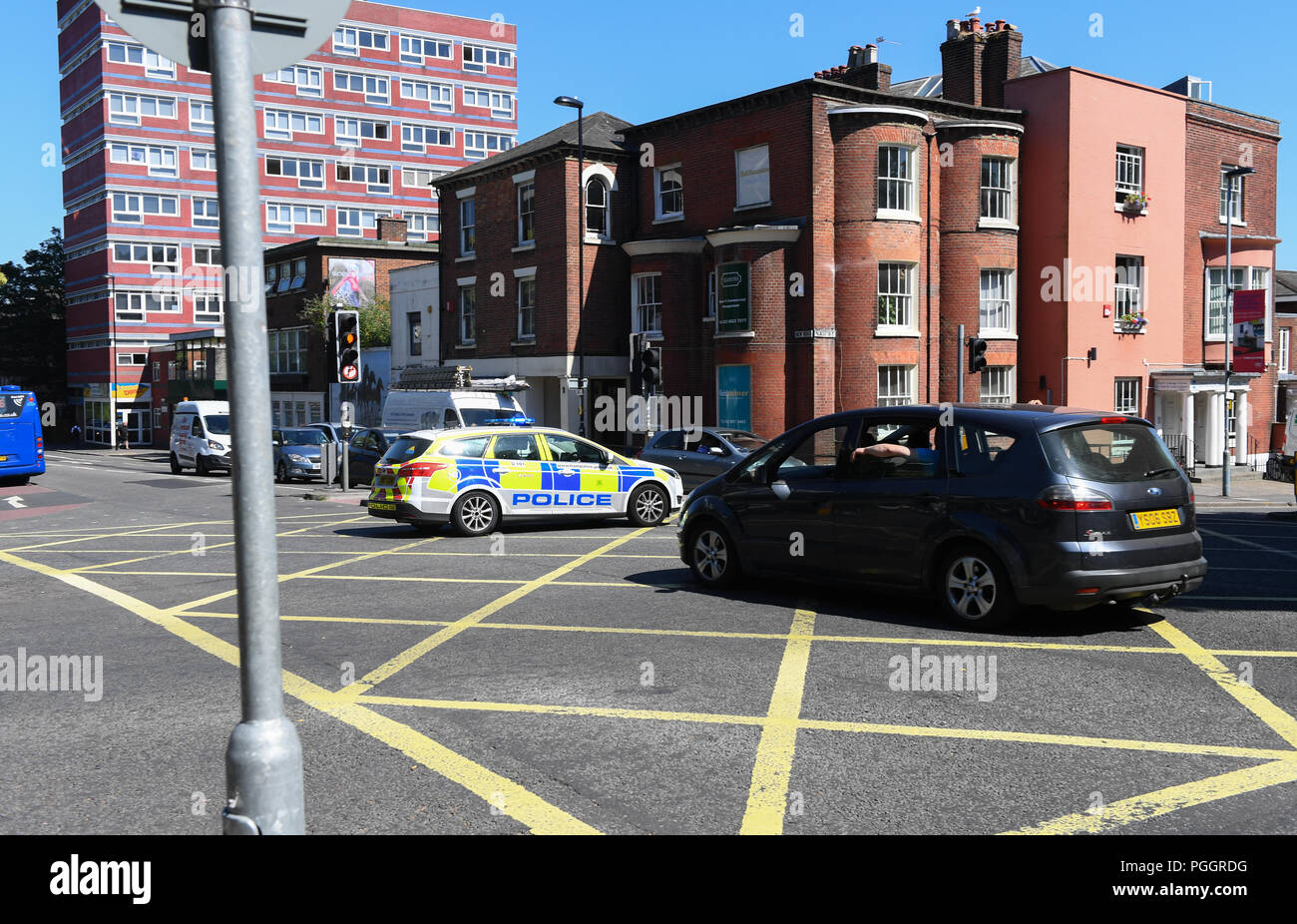 A Police vehicle enters a yellow junction box as it goes through a Red light traffic signal halting traffic on an emergency call. - Stock Image