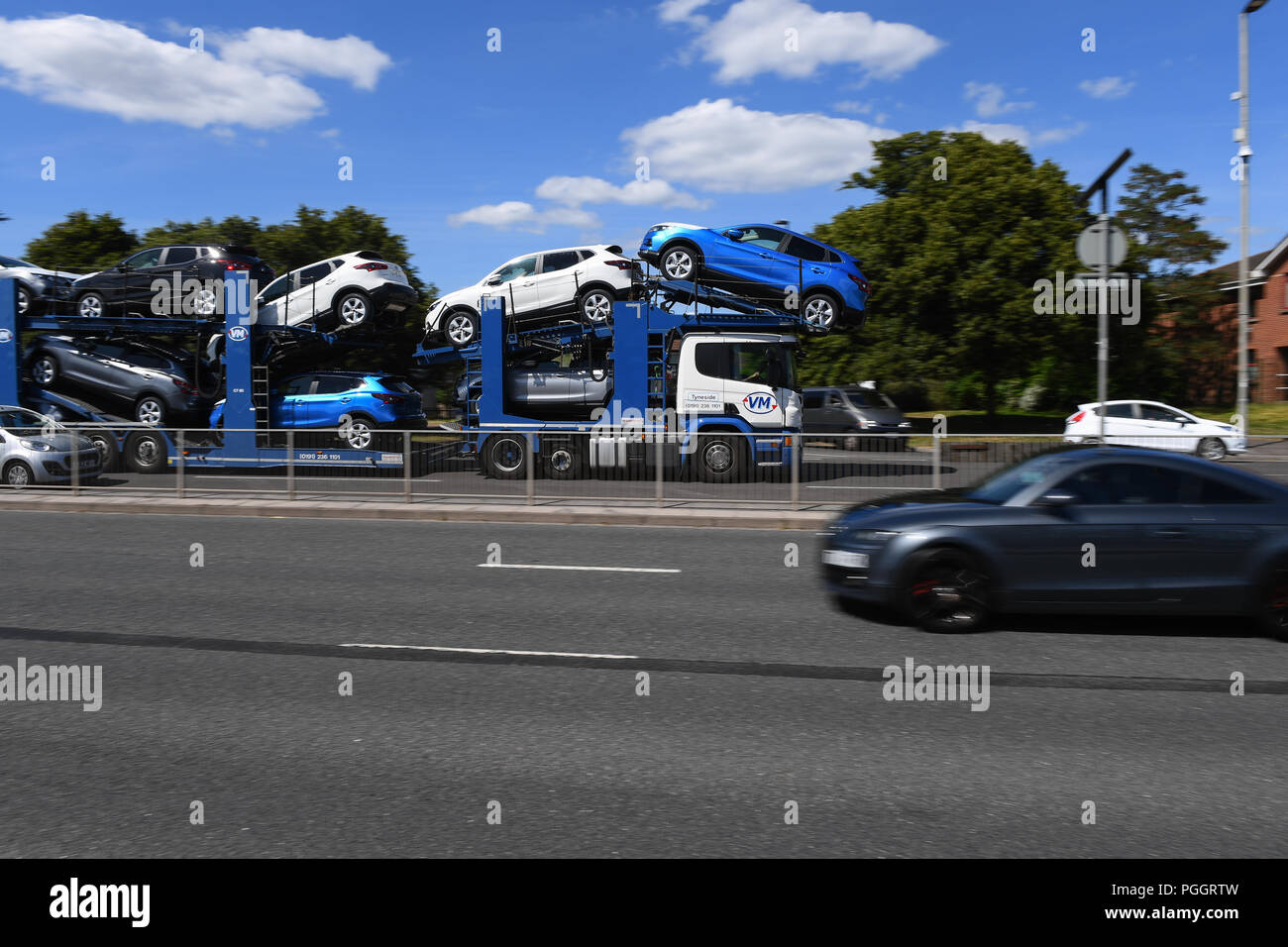A Car Transporter Drives Along A Dual Carriageway Fully