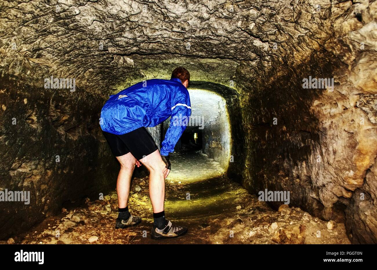 Man walk in low mystical ancient tunnel from orange sandstone. City underground. Interiors of castle catacombs - Stock Image
