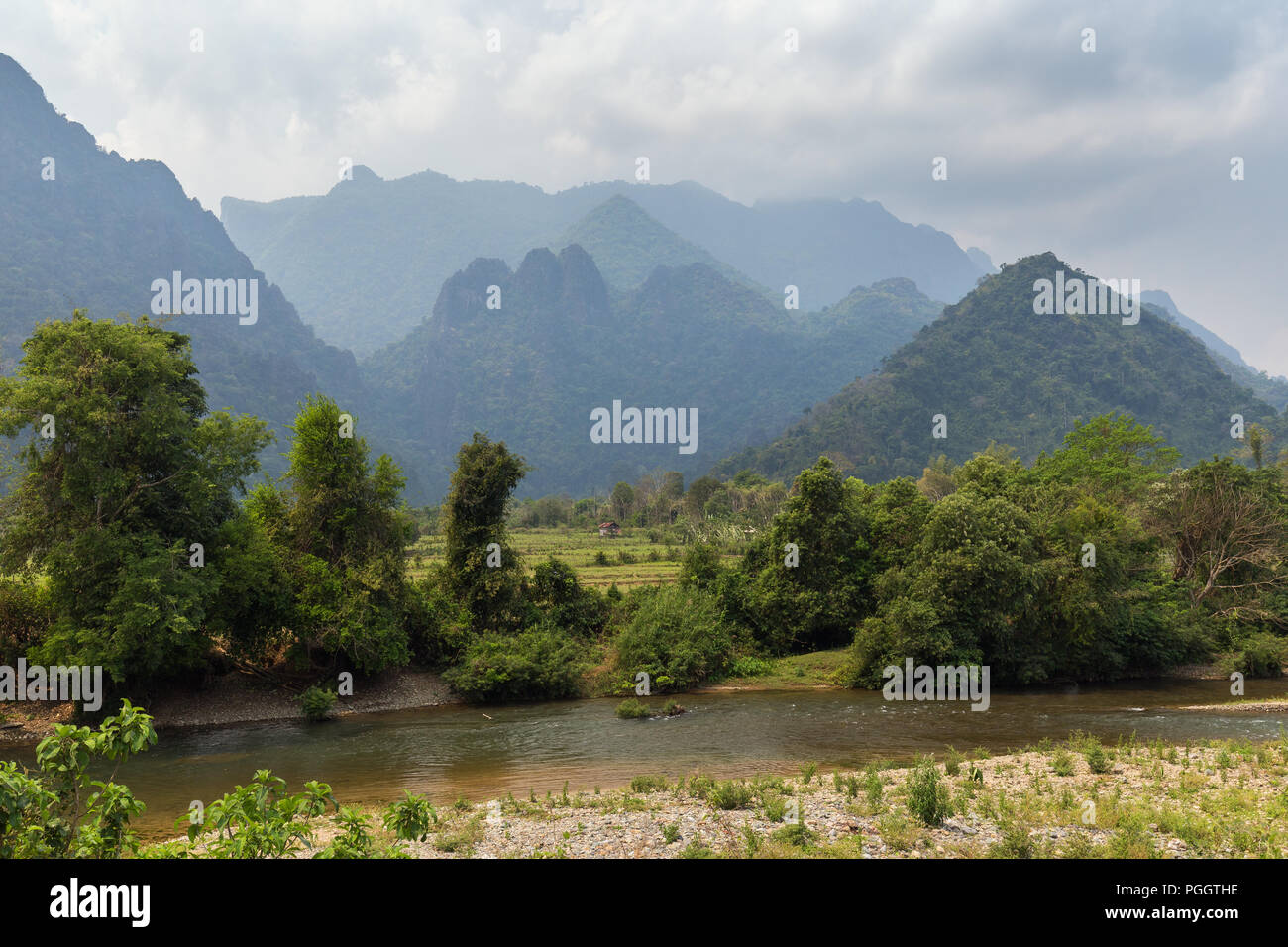 Scenic view of Nam Song River, fields and limestone mountains near Vang Vieng, Vientiane Province, Laos. - Stock Image