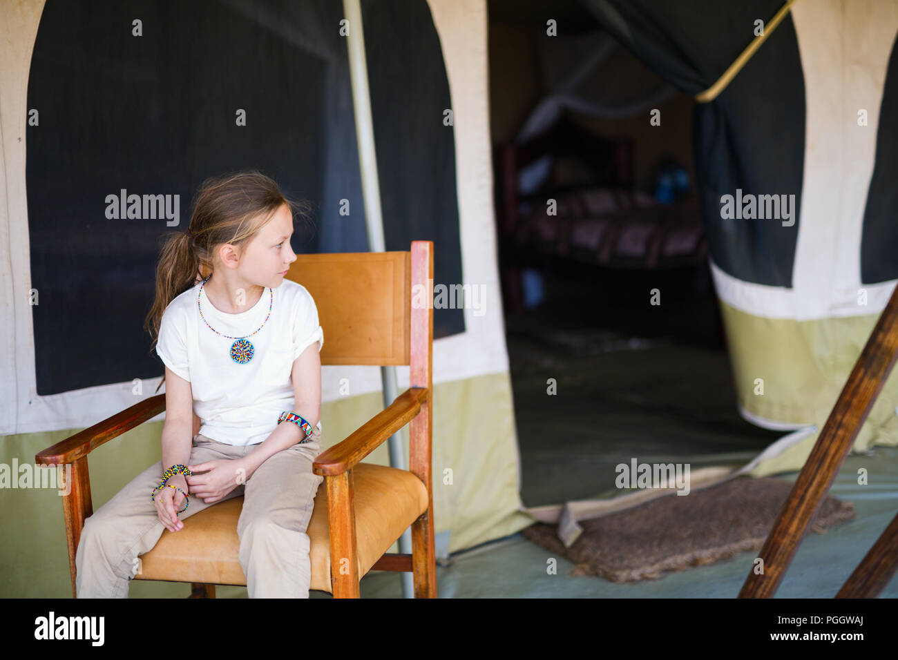 Little girl in safari tent enjoying  luxury vacation in Africa - Stock Image