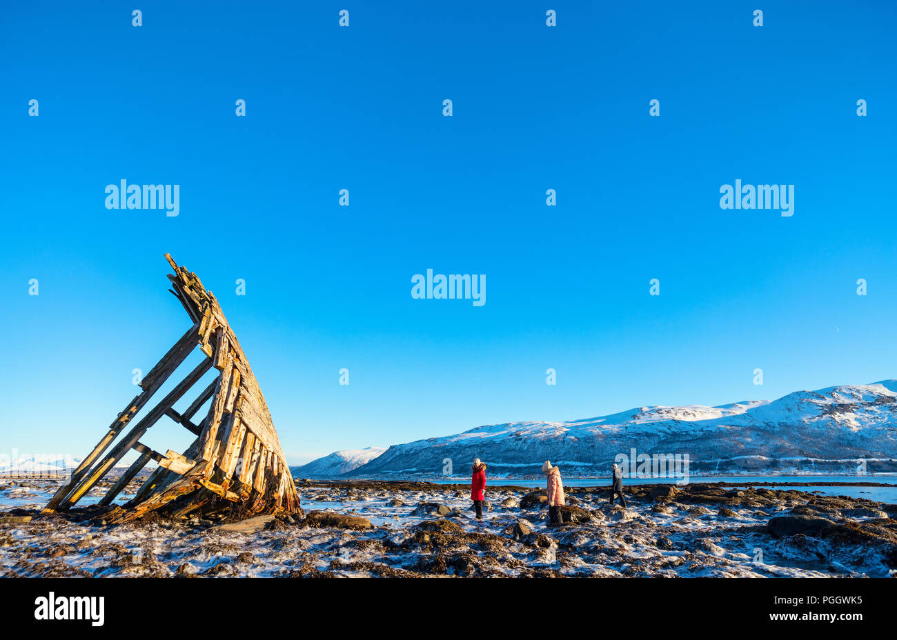 Family of mother and kids exploring shipwrecked wooden viking boat in Northern Norway - Stock Image