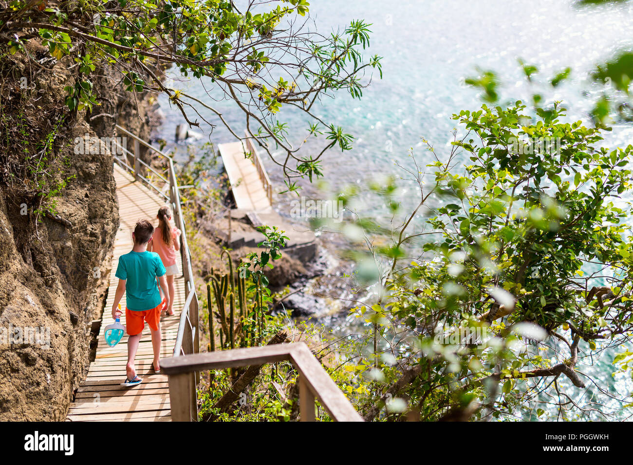 Kids brother and sister outdoors exploring tropical island on summer day - Stock Image