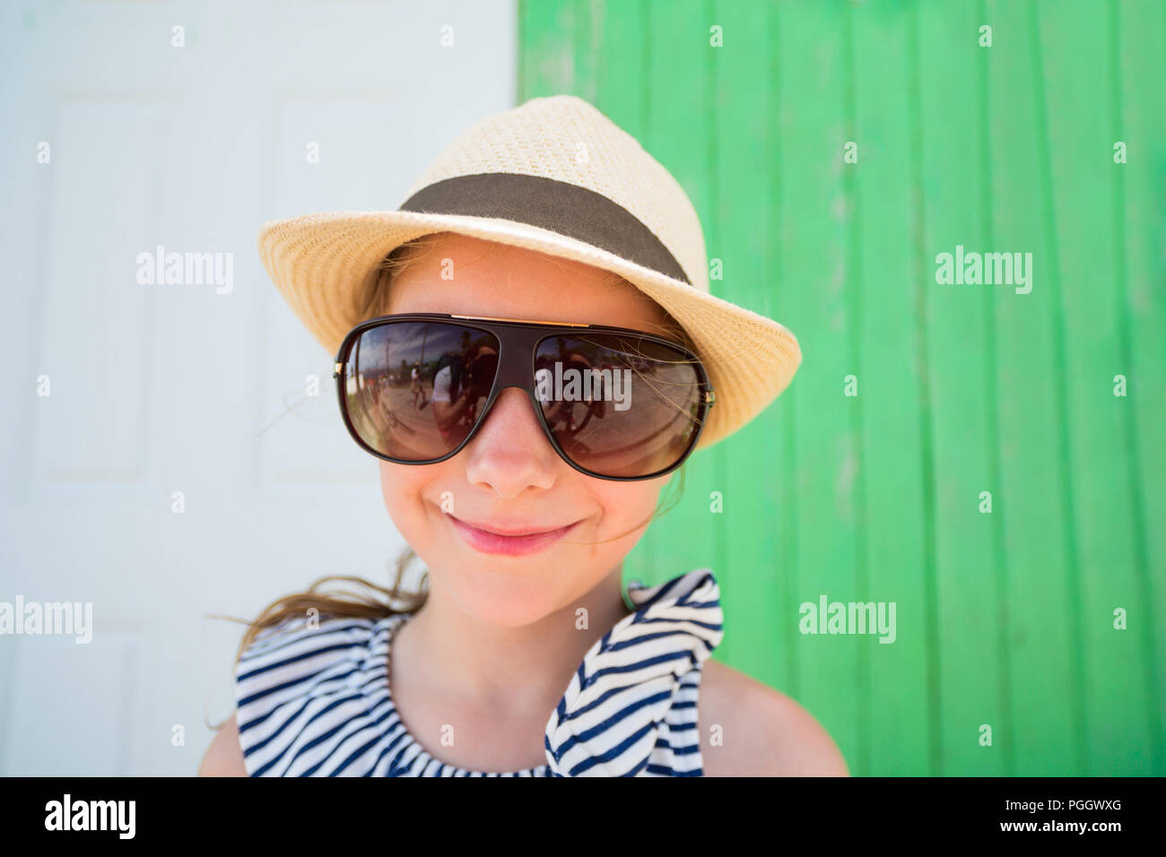 2d6fb6fc1ff9 Funny portrait of little girl wearing sun glasses and straw hat outdoors on  summer day