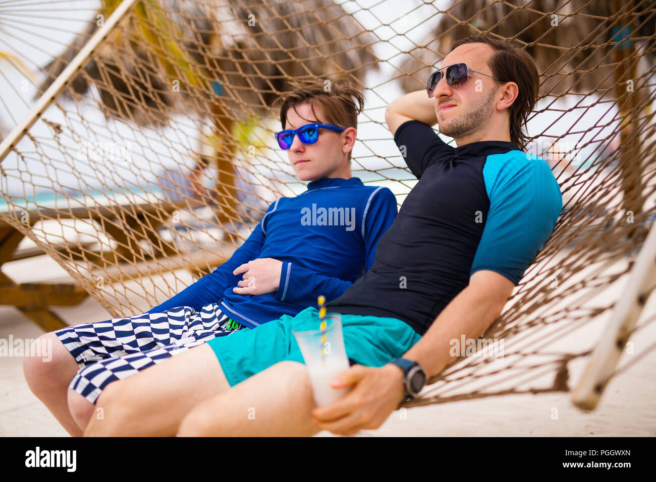 Father and his teenage son relaxing in hammock - Stock Image