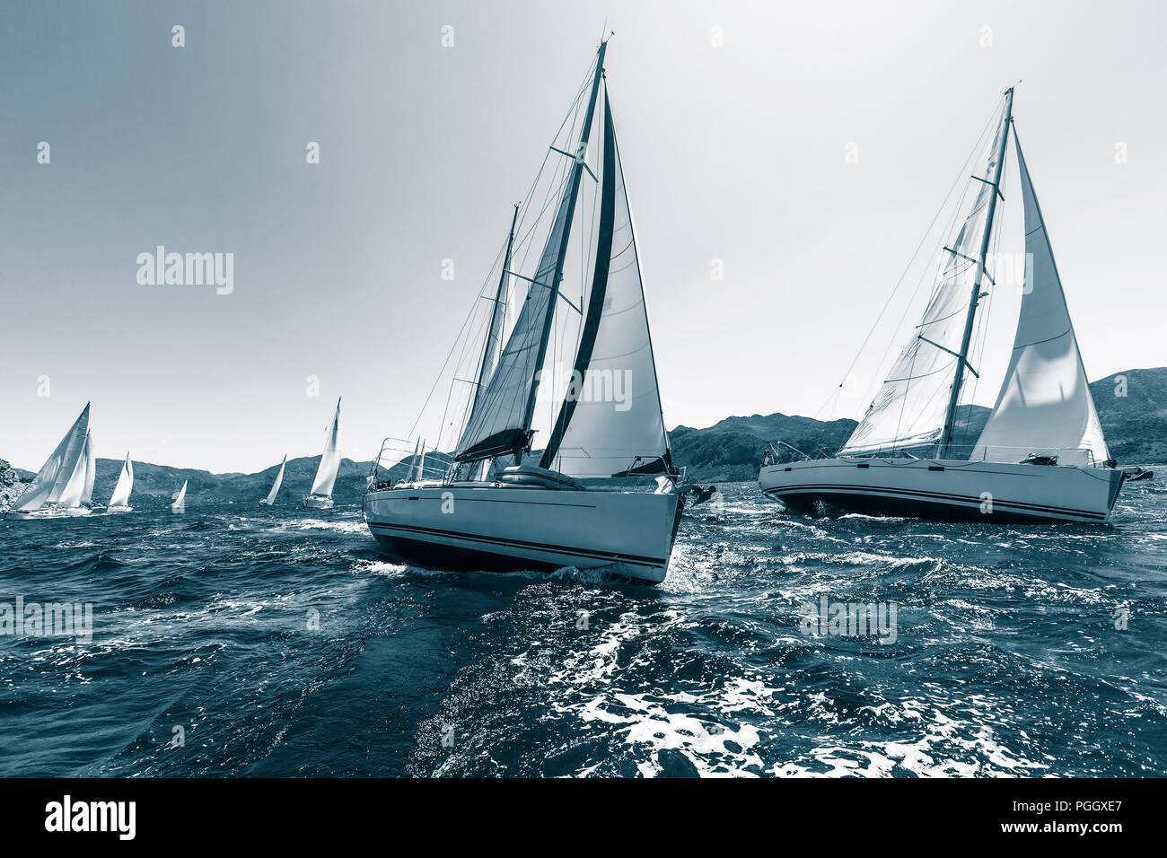 Sailing regatta through the waves in the Sea. In cool colors. - Stock Image