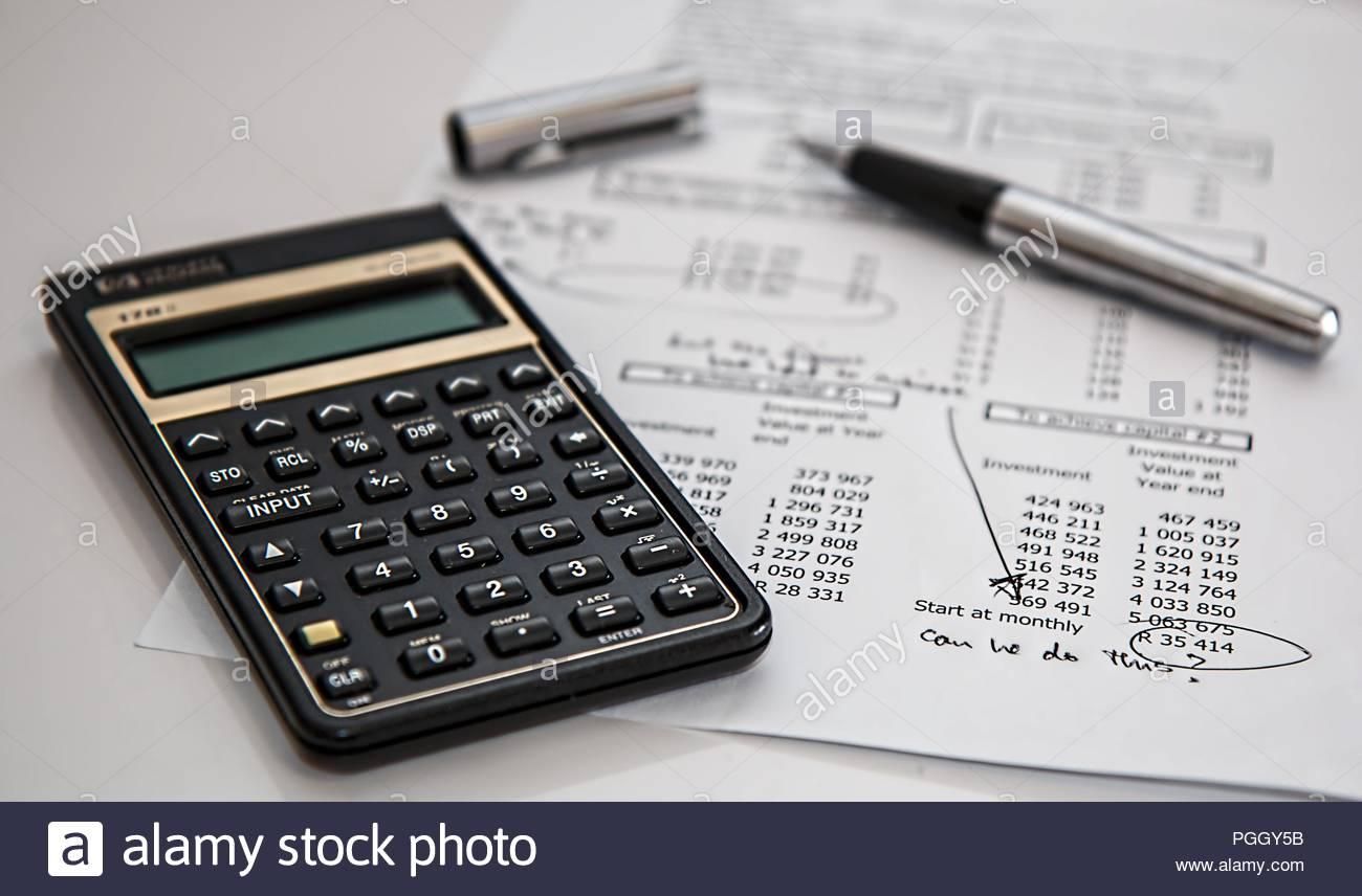 calculator on a table with pen paper counting accountant