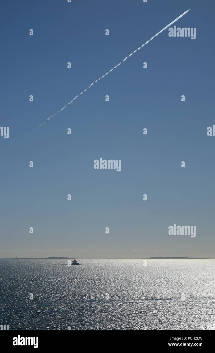 Anchored ship & jet trail over Copeland Islands, Belfast Lough, Northern Ireland. - Stock Image