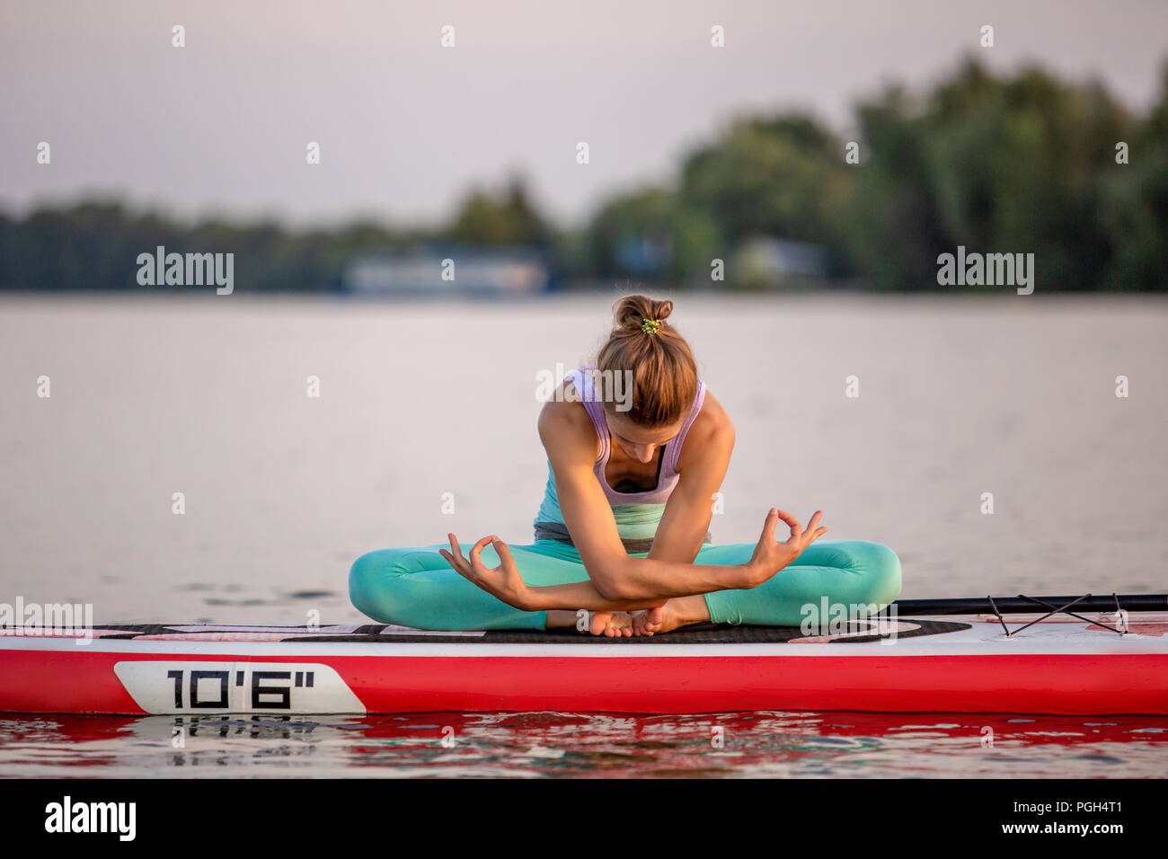 Young woman sitting on paddle board, practicing yoga pose