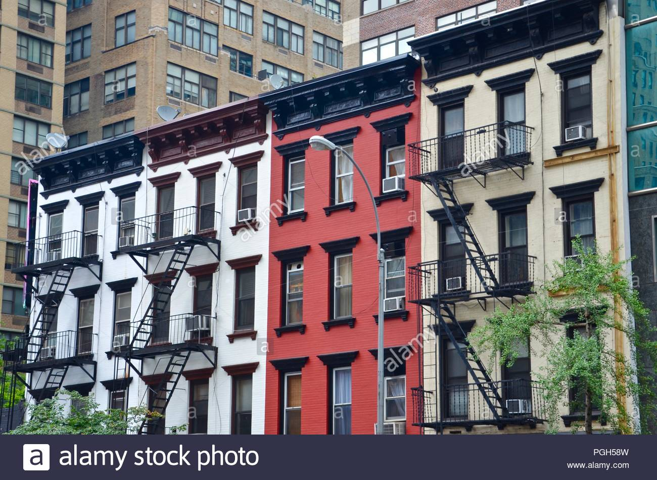 Architecture in New York City, USA, homes, living, exterior design, sunny, vacation, windows, fire escape stairways, investment, colorful, expensive - Stock Image