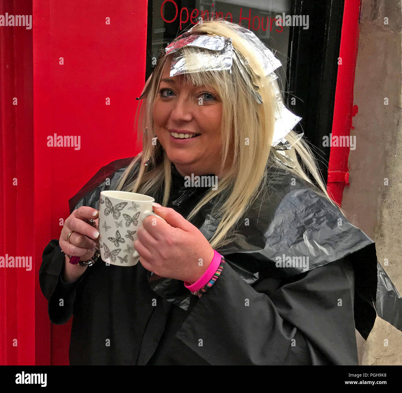 Woman having hair coloured, outside hair salon, Perth, Scotland, UK - Stock Image