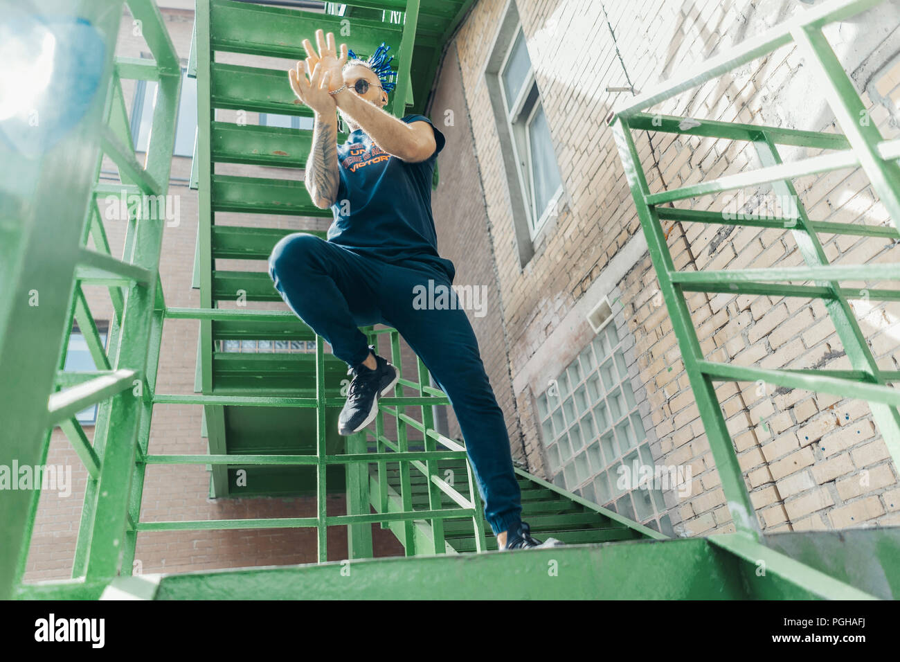 Young man with blue dreadlocks dancing reggaeton on green stairs. Man is on focus and foreground, green stairs is on background and blurred. - Stock Image