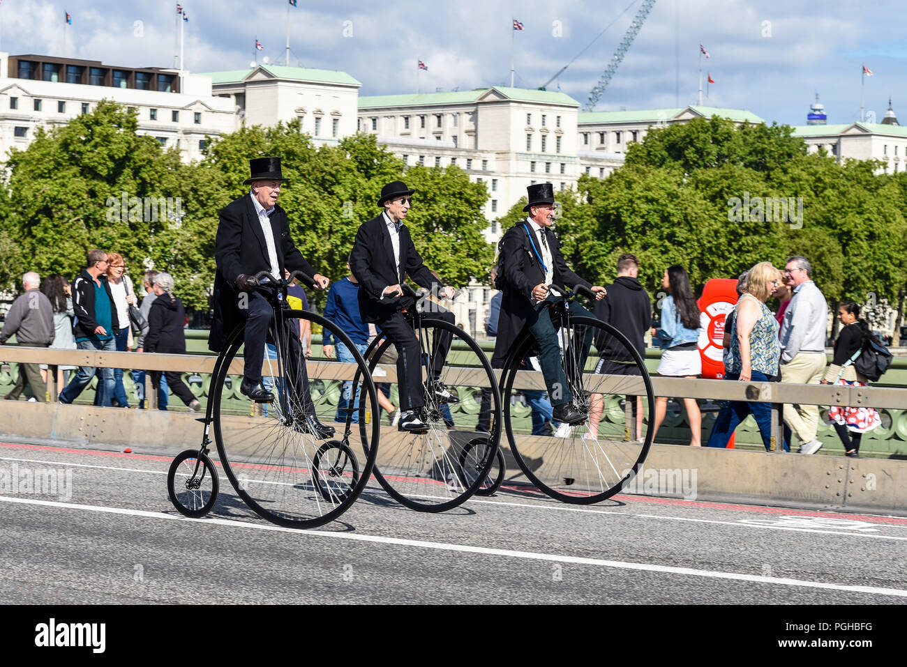 Three penny farthing cyclists ride across Westminster Bridge, London, UK. Gentlemen riders. Penny farthings by UDC, unicycle dot com. Top hats - Stock Image