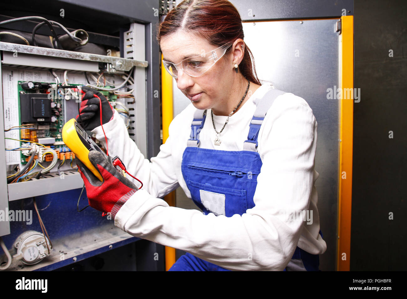 female electrician fixing an engine control panel Stock Photo