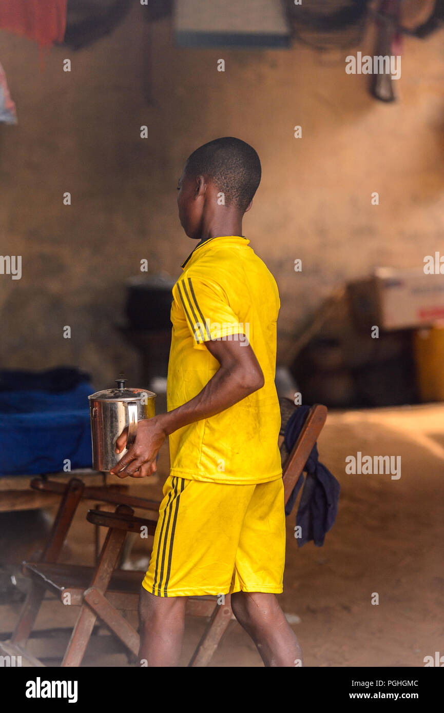 LOME, TOGO - Jan 9, 2017: Unidentified Togolese young boy holds a stewpot in the local shaman's house. Togo children suffer of poverty due to the bad  - Stock Image