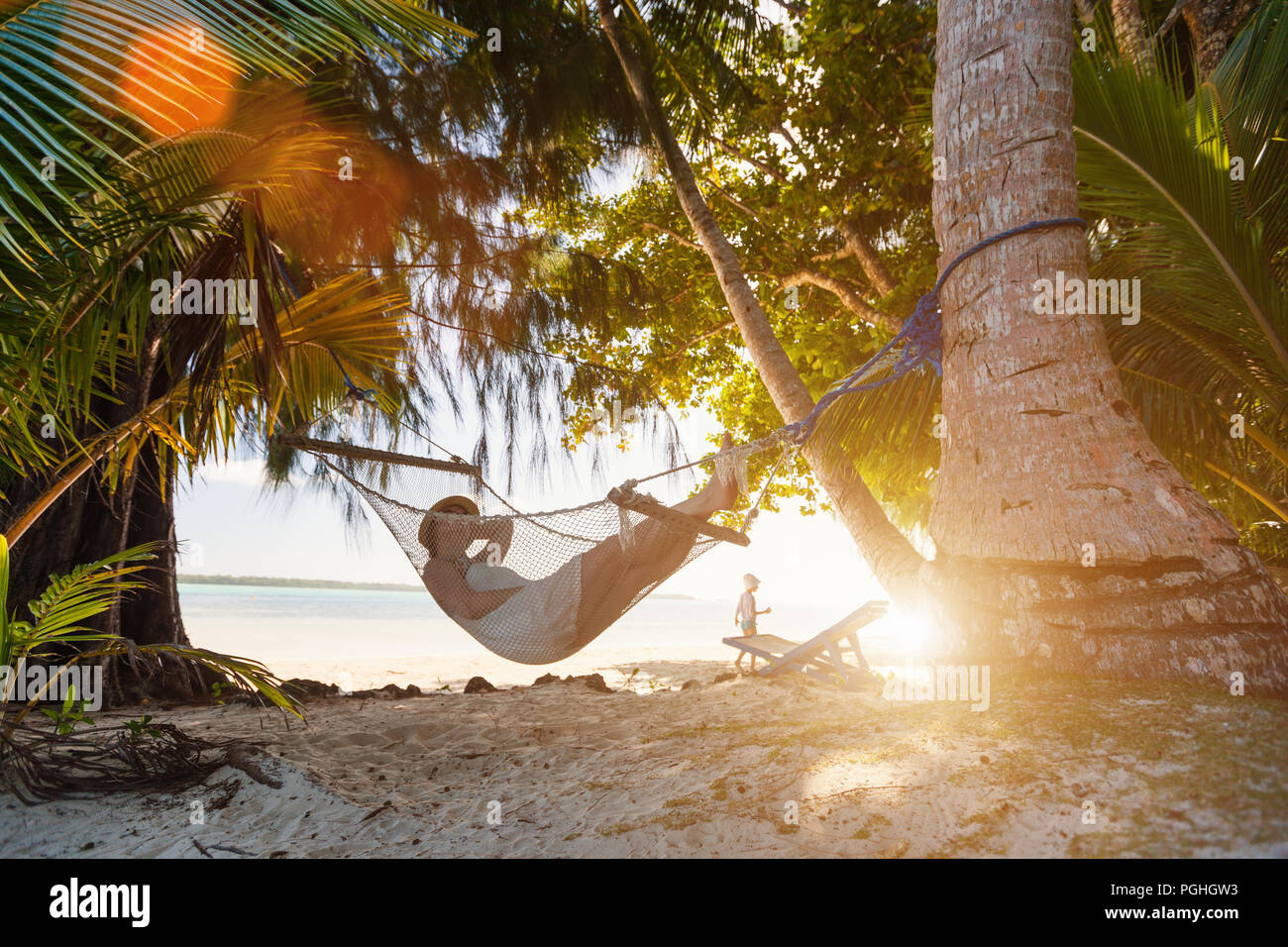 Young beautiful woman relaxing in hammock at tropical beach during sunset - Stock Image