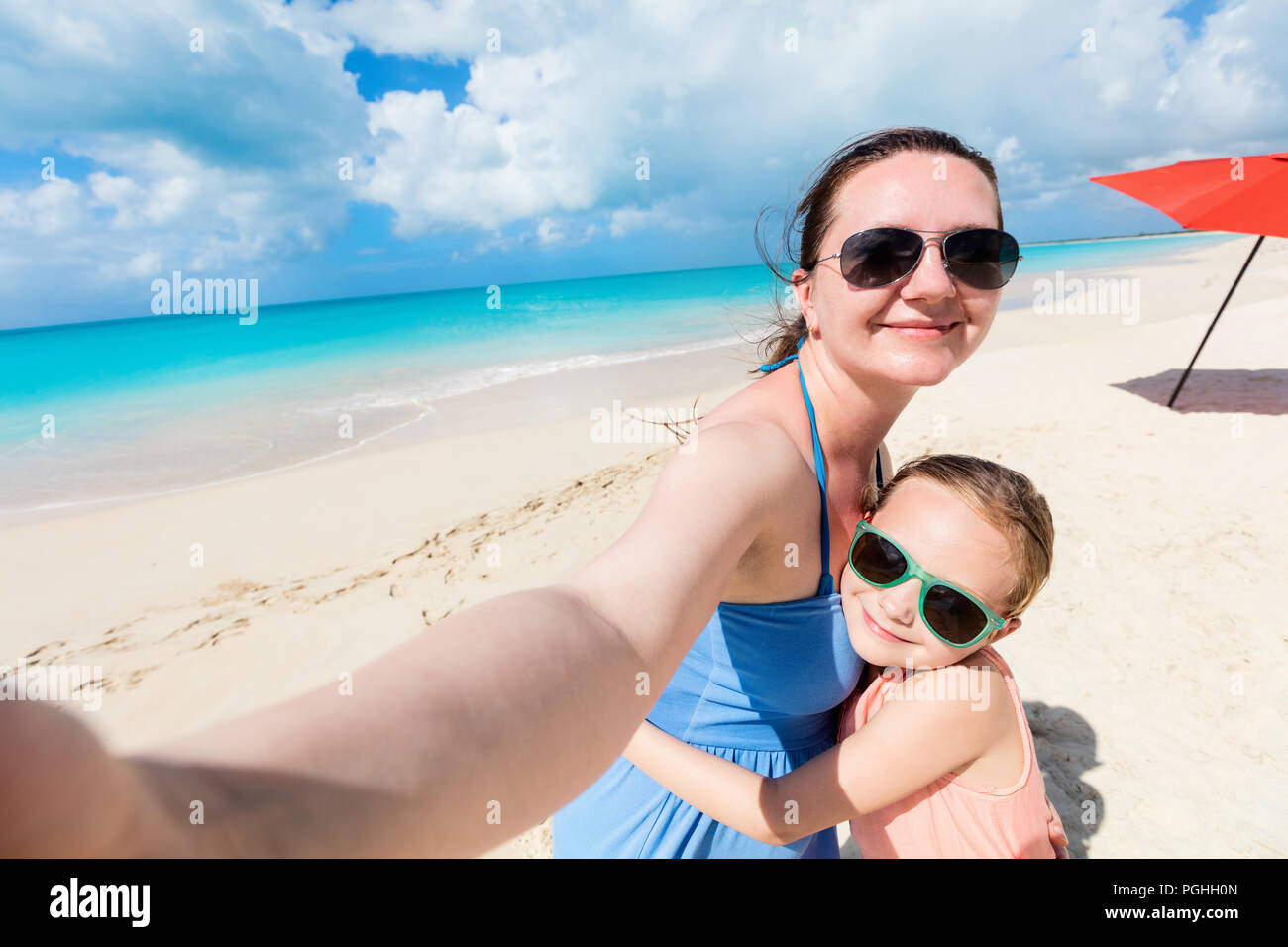 Happy family mother and her adorable little daughter at beach taking selfie Stock Photo