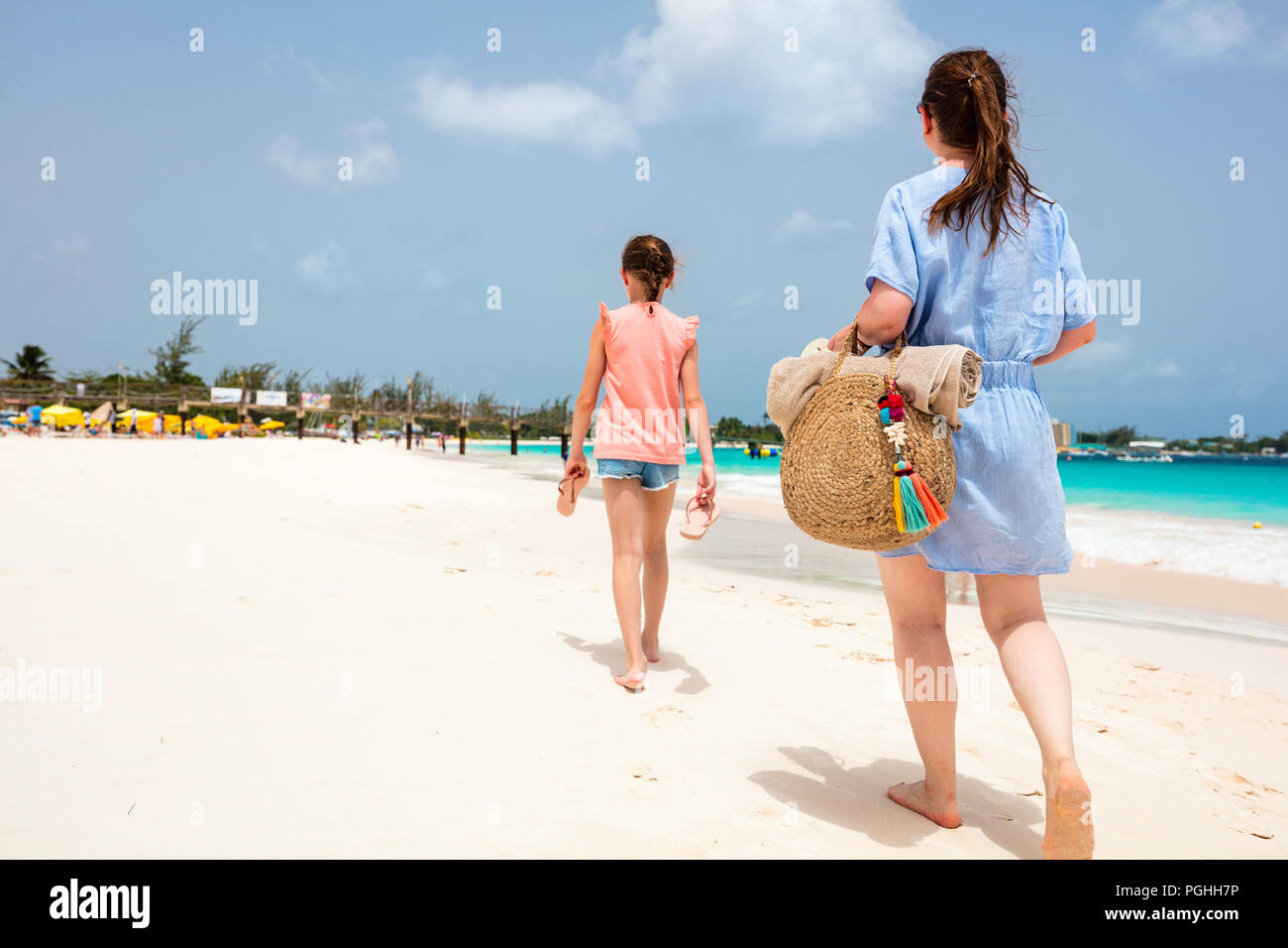 8384359b840df Back view family mother and daughter walking at beach in Barbados enjoying  tropical summer vacation