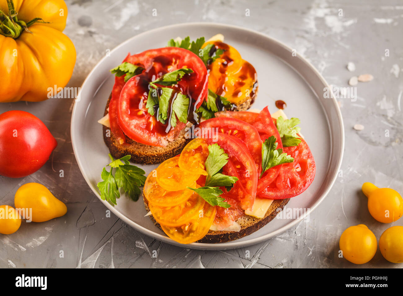 Sandwiches with tomatoes and cheese on gray plate, top view. Clean eating concept. Stock Photo