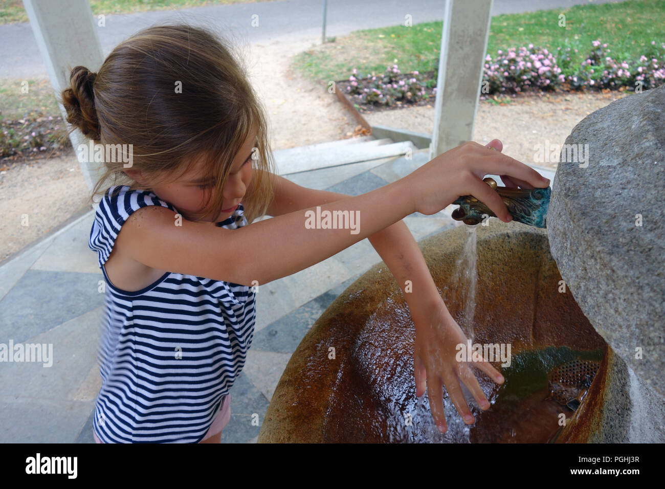 Young girl at a mineral spring fountain tap in spa town Karlovy Vary Czech Republic Stock Photo
