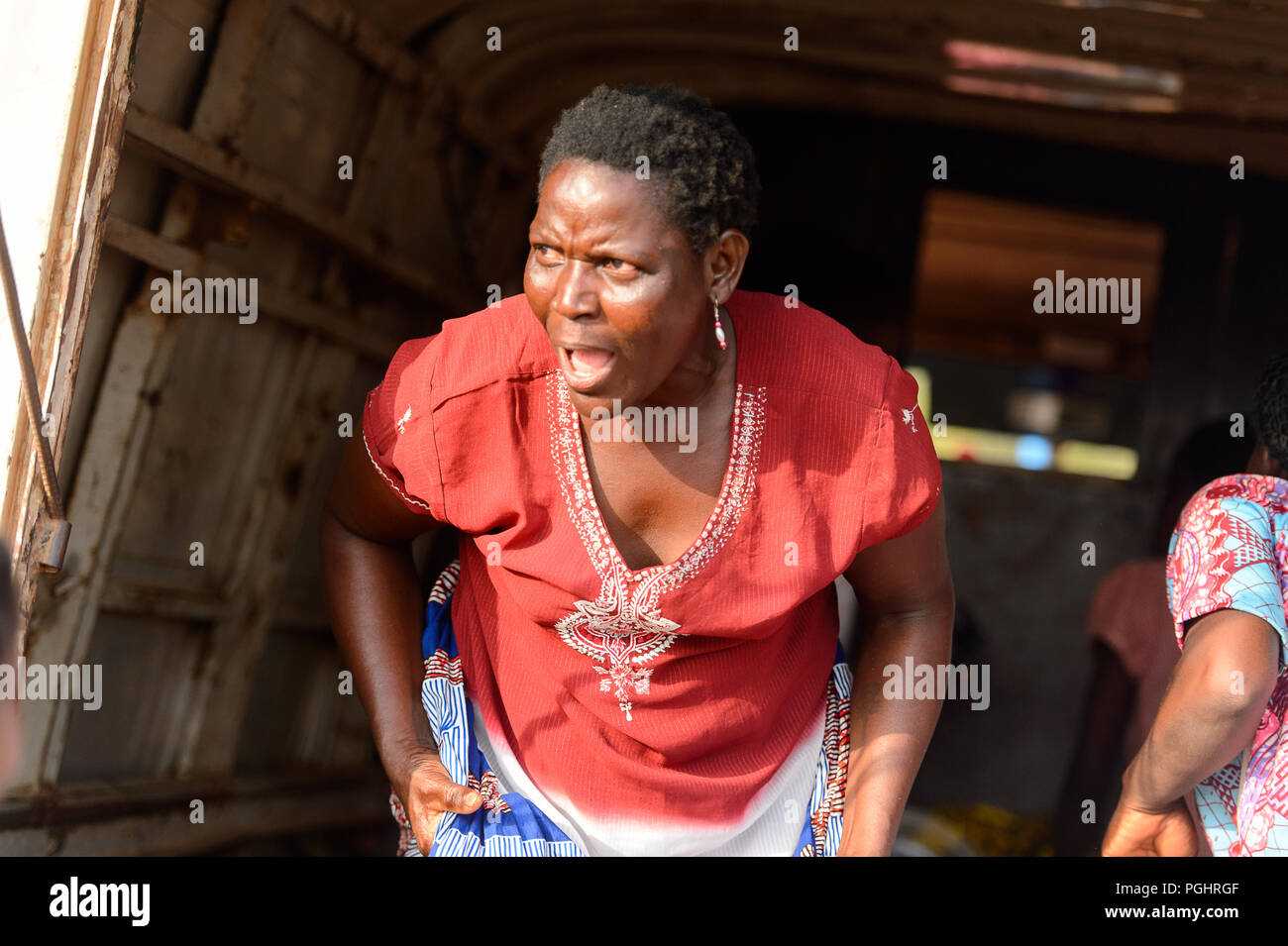 OUIDAH, BENIN - Jan 10, 2017: Unidentified Beninese woman tries to say something at the local market. Benin people suffer of poverty due to the bad ec - Stock Image