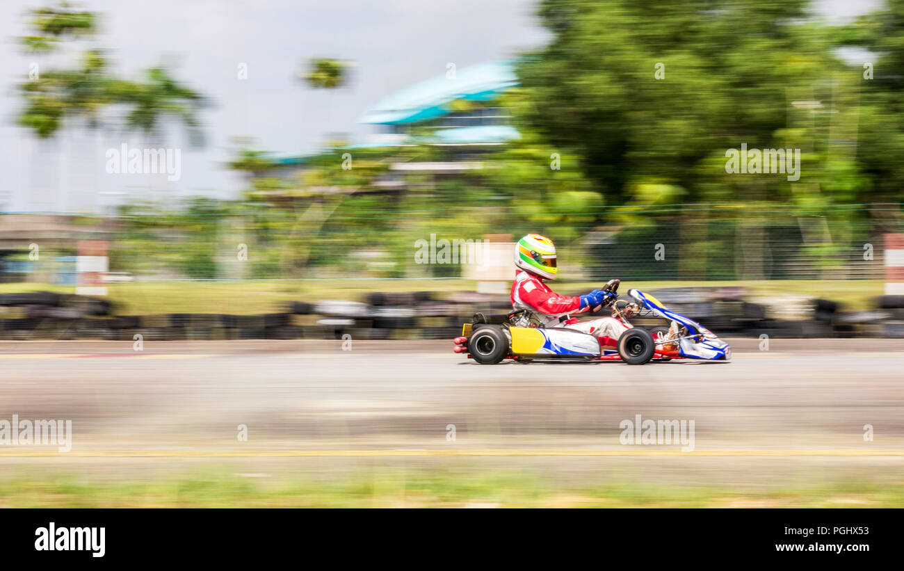 A professional racer with racing suit in his go-kart competing at City Karting racing track under a hot weather, shot with panning the camera towards  - Stock Image
