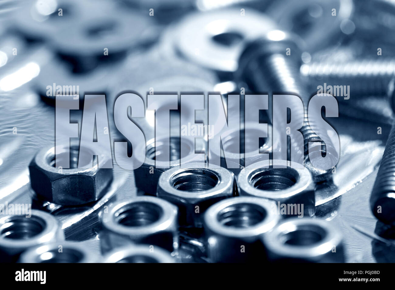 Fasteners written on top of nuts and bolts in blue background Stock Photo