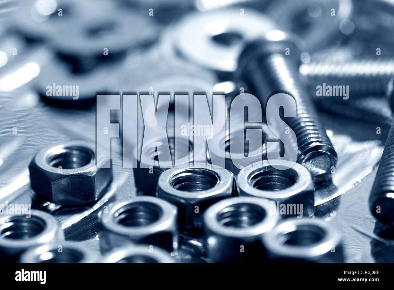 Fixings written on top of nuts and bolts in blue background - Stock Image