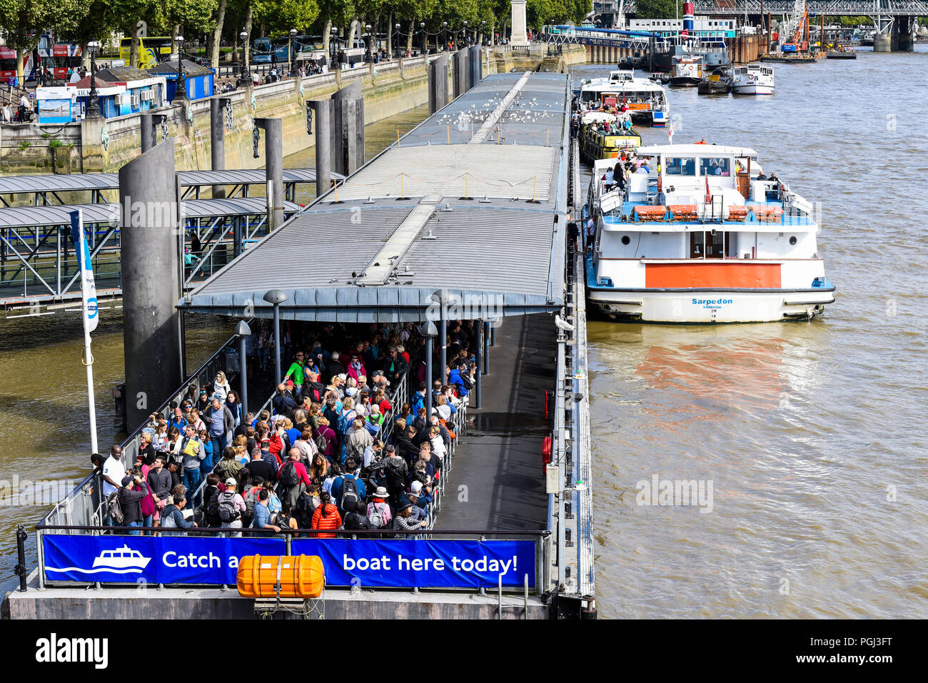 Westminster Pier jetty, Victoria Embankment, London, UK. Passengers queue to embark on a river bus, riverbus on the River Thames. Sarpedon vessel - Stock Image