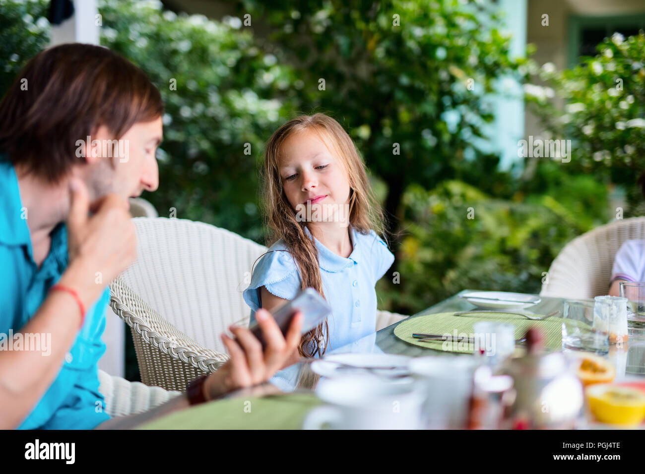 Happy family of father and his adorable daughter in  outdoor restaurant - Stock Image