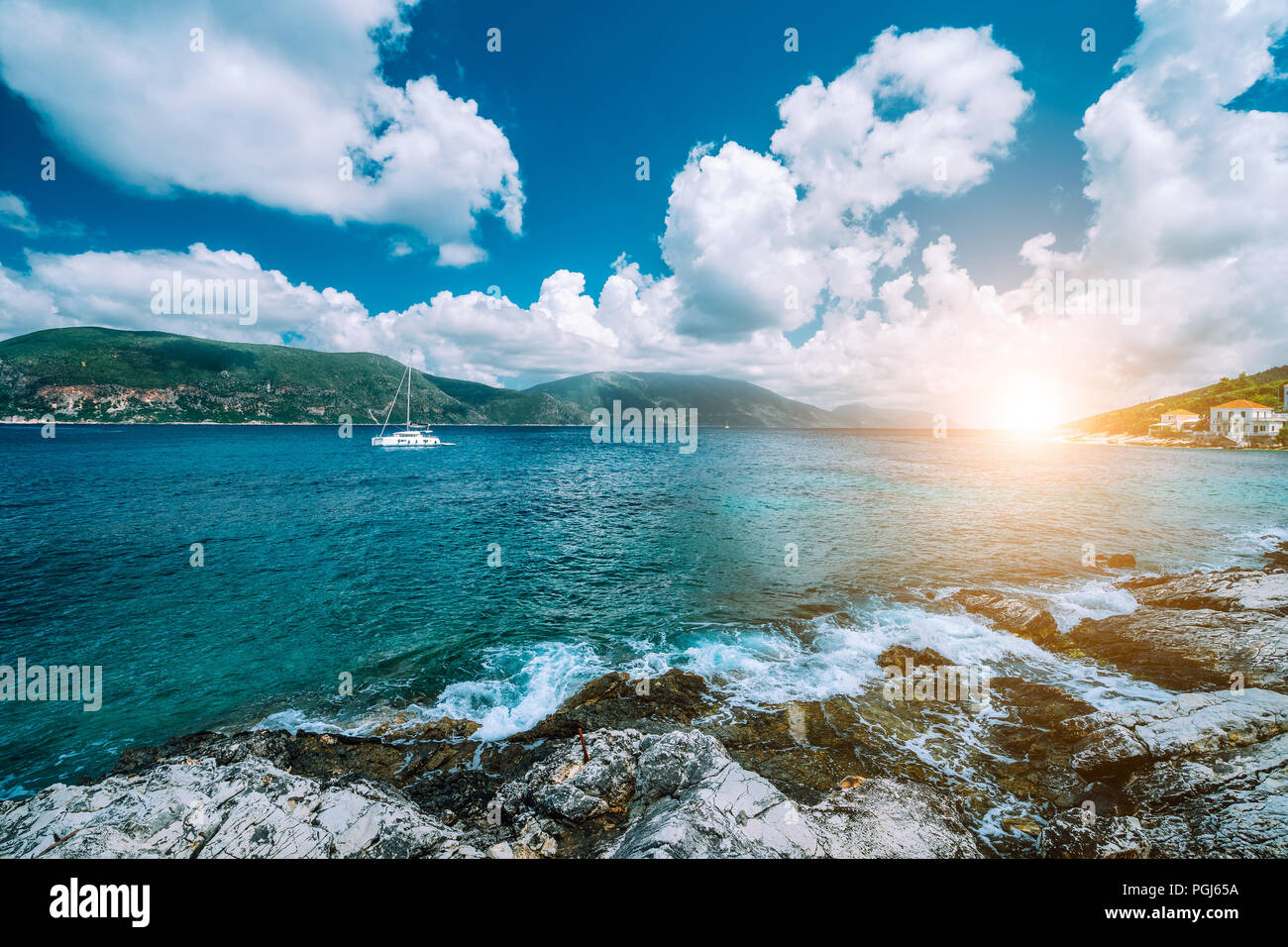 Crystal clear transparent blue turquoise teal Mediterranean sea water in Fiskardo town. White yacht in open sea at anchor under amazing white clouds and sun light, Kefalonia, Ionian islands, Greece - Stock Image