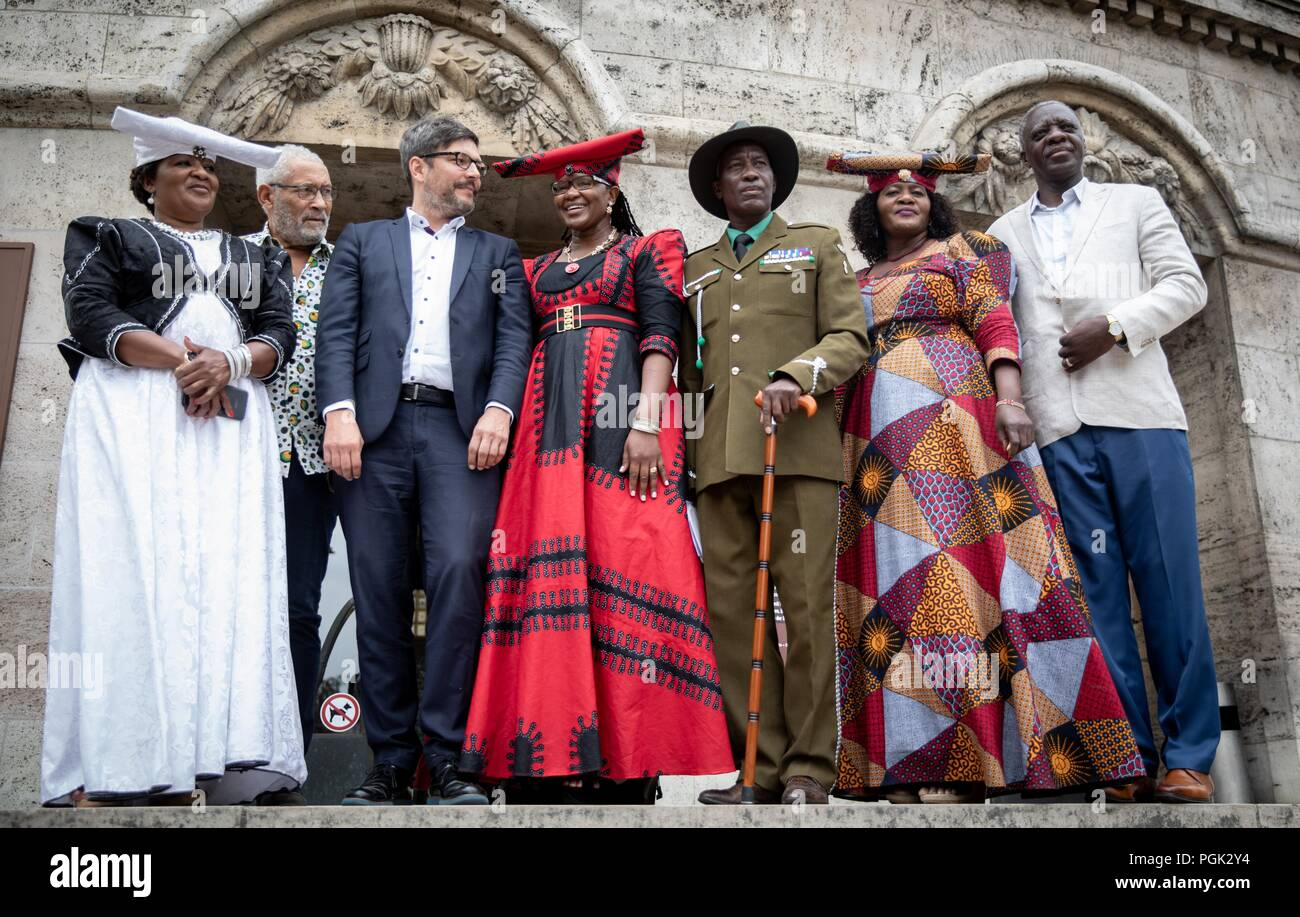Germany, Berlin. 27th Aug, 2018. Dirk Behrendt (3rd from left, Alliance 90/The Greens), Berlin Senator of Justice, receives a delegation of Ovaherero and Nama from Namibia, with Esther Utjiua Muinjangue (l), President of the Ovaherero Genocide Foundation in Namibia, and other participants before the Senate Administration for Justice, Consumer Protection and Anti-Discrimination. This week, stolen remains of Herero and Nama murdered in the 1904-08 genocide are to be returned to a government delegation from Namibia. Credit: Kay Nietfeld/dpa/Alamy Live News - Stock Image