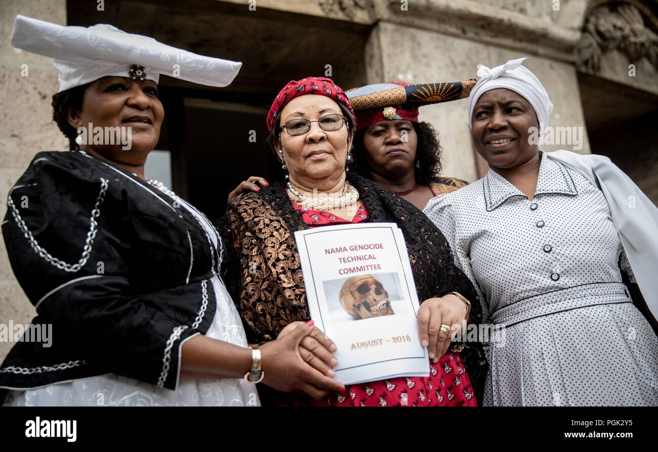 27 August 2018, Berlin, Germany: A delegation of Ovaherero and Nama from Namibia, Esther Utjiua Muinjangue (l), President of the Ovaherero Genocide Foundation in Namibia, Ida Hoffmann (2nd from left), Member of Parliament and Chairwoman of the Nama Genocide Technical Committee in Namibia and other delegation members are standing before the Senate Administration for Justice, Consumer Protection and Anti-Discrimination after a meeting and a press conference with Senator Behrendt (not shown). This week, stolen remains of Herero and Nama murdered in the 1904-08 genocide are to be returned to a gov - Stock Image