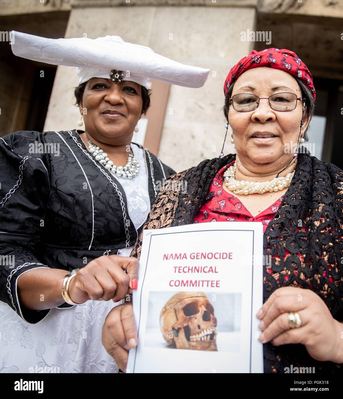 27 August 2018, Berlin, Germany: A delegation of Ovaherero and Nama from Namibia with Esther Utjiua Muinjangue (l), Chairwoman of the Ovaherero Genocide Foundation in Namibia, and Ida Hoffmann (r), Member of Parliament and Chairwoman of the Nama Genocide Technical Committee in Namibia, are standing before the Senate Administration for Justice, Consumer Protection and Anti-Discrimination after a meeting and a press conference with Senator Behrendt (not shown). This week, stolen remains of Herero and Nama murdered in the 1904-08 genocide are to be returned to a government delegation from Namibia - Stock Image