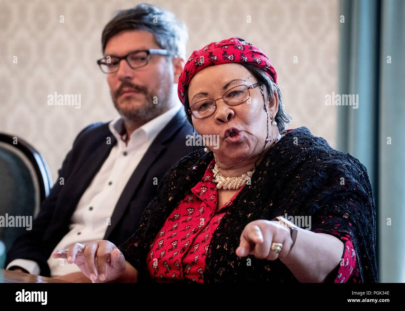 Germany, Berlin. 27th Aug, 2018. Dirk Behrendt (l, Alliance 90/The Greens), Berlin Senator of Justice, and Ida Hoffmann, Member of Parliament and Chairwoman of the Nama Genocide Technical Committee in Namibia, participate in a press conference with a delegation of Ovaherero and Nama from Namibia. This week, stolen remains of Herero and Nama murdered in the 1904-08 genocide are to be returned to a government delegation from Namibia. Credit: Kay Nietfeld/dpa/Alamy Live News - Stock Image