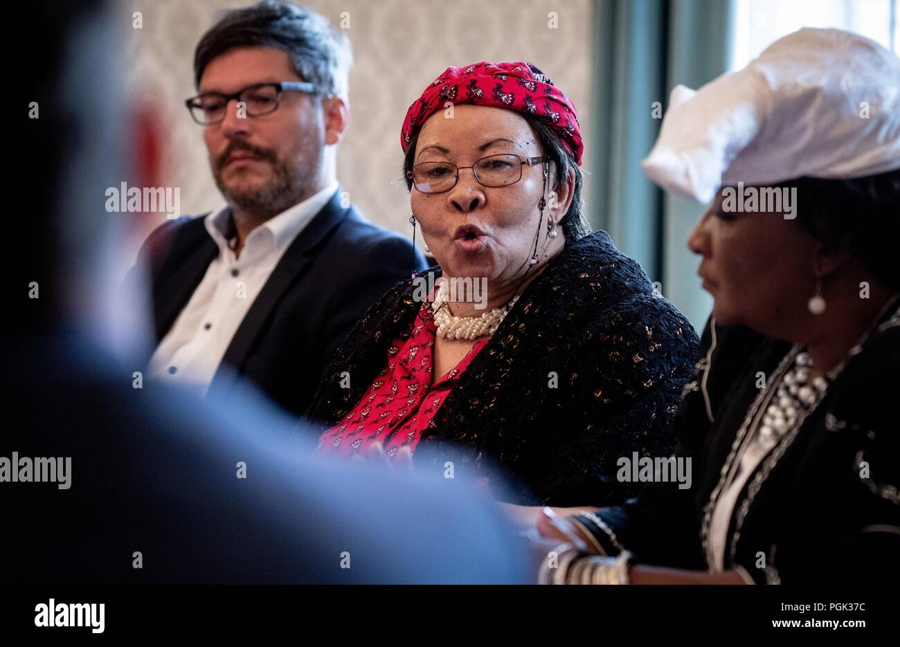 Germany, Berlin. 27th Aug, 2018. Dirk Behrendt (l, Alliance 90/The Greens), Berlin Senator of Justice, attends a press conference with a delegation of Ovaherero and Nama from Namibia, with Ida Hoffmann (M), Member of Parliament and Chair of the Nama Genocide Technical Committee in Namibia, and Esther Utjiua Muinjangue (r), Chair of the Ovaherero Genocide Foundation in Namibia. This week, stolen remains of Herero and Nama murdered in the 1904-08 genocide are to be returned to a government delegation from Namibia. Credit: Kay Nietfeld/dpa/Alamy Live News - Stock Image
